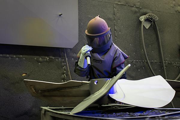 Mitarbeiter beim Arbeiten mit Glasperlenstrahl
